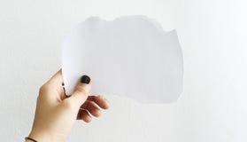 Hand, die ein weißes unbelegtes Papier anhält lizenzfreie stockbilder