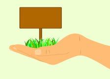 Hand, die ein Zeichen im Gras hält Stockfotos