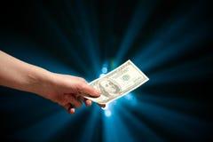 Hand, die eine 100-Dollar-Banknote gibt Stockfotografie