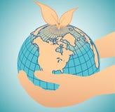 Hand, die eine blaue Erdekugel anhält Lizenzfreies Stockbild