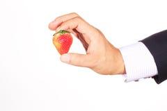 Hand, die eine Erdbeere anhält Stockfotos