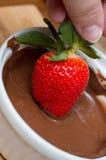 Hand, die eine Erdbeere in der Schokolade eintaucht Lizenzfreie Stockfotos