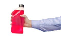 Hand, die eine Flasche Frostschutzmittel hält stockbild