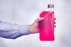 Hand, die eine Flasche Frostschutzmittel hält lizenzfreie stockfotos
