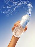 Hand, die eine Flasche Wasser anhält Stockfoto