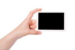 Hand, die eine Fotographie anhält Stockbild