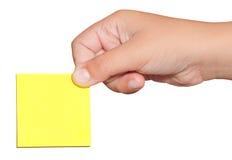 Hand, die eine gelbe Aufkleberpost-itanmerkung anhält Stockbild