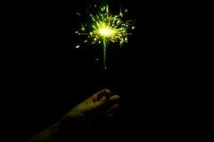 Hand, die eine gelbe lodernde Wunderkerze hält Lizenzfreie Stockfotografie