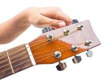 Hand, die eine Gitarre vom Spindelkasten abstimmt. Lizenzfreie Stockfotografie