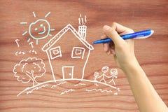 Hand, die eine glückliche Familie auf Holz zeichnet Lizenzfreie Stockfotos