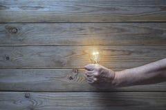 Hand, die eine Glühlampe anhält Stockbild