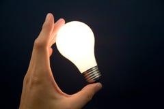 Hand, die eine helle Glühlampe anhält Stockfotos