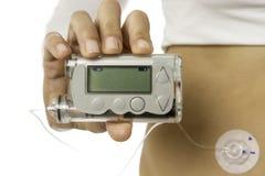 Hand, die eine insuline Pumpe hält Lizenzfreie Stockfotos