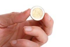 Hand, die eine Münze anhält. Stockfotografie