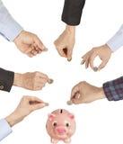 Hand, die eine Münze in moneybox einsetzt Lizenzfreies Stockbild