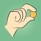 Hand, die eine Münze zwischen zwei Fingern hält Lizenzfreie Stockfotografie