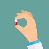 Hand, die eine Pille anhält Lizenzfreies Stockbild