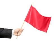 Hand, die eine rote Fahne anhält Lizenzfreies Stockbild