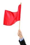 Hand, die eine rote Fahne wellenartig bewegt Lizenzfreies Stockfoto
