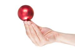 Hand, die eine rote Weihnachtskugel anhält Lizenzfreie Stockfotografie