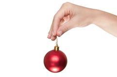 Hand, die eine rote Weihnachtskugel anhält Lizenzfreies Stockfoto
