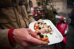 Hand, die eine Scheibe der italienischen Pizza hält Stockfoto