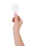 Hand, die eine weißglühende Glühlampe anhält Stockbild