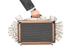 Hand, die einen Aktenkoffer voll vom Geld hält Lizenzfreie Stockfotografie