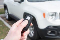 Hand, die einen Autoalarmschlüssel mit diebstahlsicherem hält Stockbilder