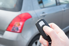 Hand, die einen Autoalarmschlüssel mit diebstahlsicherem hält Stockfoto