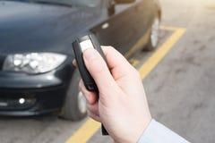 Hand, die einen Autoalarmschlüssel mit diebstahlsicherem hält Stockbild