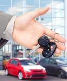 Hand, die einen Autoschlüssel gibt Lizenzfreies Stockbild