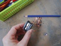 Hand, die einen Bleistiftspitzer schärft Stockbild