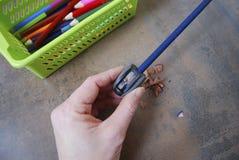 Hand, die einen Bleistiftspitzer schärft Lizenzfreies Stockbild