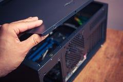 Hand, die einen Computerkasten öffnet Lizenzfreies Stockbild