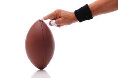 Hand, die einen Fußball betriebsbereit zum Treten anhält Lizenzfreie Stockfotos