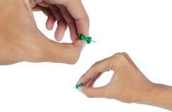 Hand, die einen grünen Thumbtack anbringt Lizenzfreies Stockfoto