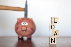 Hand, die einen Hammer über einem Sparschwein und das Wort DARLEHEN geschrieben auf hölzerne Würfel hält lizenzfreie stockfotos
