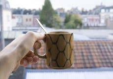 Hand, die einen heißen Tasse Kaffee hält stockbilder