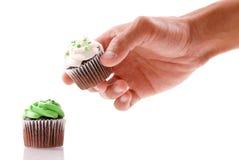 Hand, die einen kleinen Kuchen erhält stockbilder