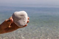 Hand, die einen natürlichen Herz-förmigen Stein hält stockfoto