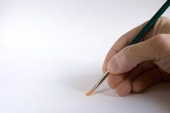 Hand, die einen Pinsel anhält Stockbilder