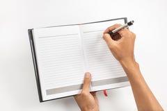 Hand, die einen Stift und ein Notizbuch hält stockfotografie