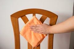 Hand, die einen Stuhl abwischt Lizenzfreie Stockfotos