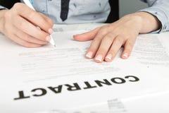 Hand, die einen Vertrag unterzeichnet Stockbilder