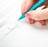 Hand, die einen Vertrag unterzeichnet Lizenzfreie Stockbilder