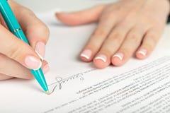 Hand, die einen Vertrag unterzeichnet Lizenzfreies Stockbild