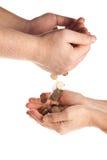 Hand, die einer anderen Person eine Münze gibt Stockfotografie