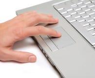 Hand, die an einer Laptopberührungsfläche arbeitet Stockfotografie