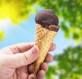 Hand, die Eiscreme mit Schokolade hält Lizenzfreie Stockfotografie